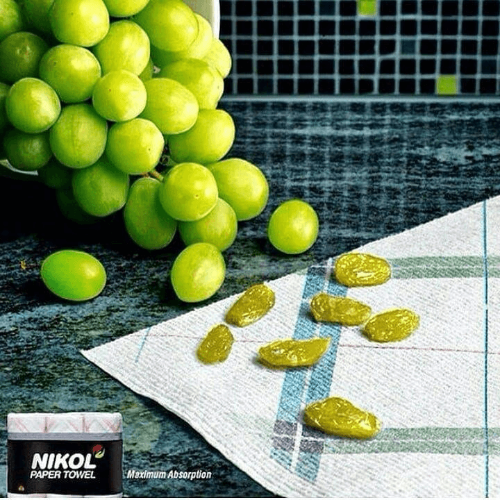 Nikol Paper Towels Ad that shows dried grapes, implying it sucked the moisture out of them to turn them into raisins
